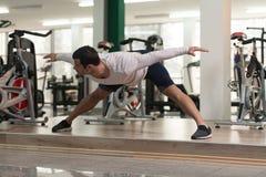 Allungamenti dell'uomo di forma fisica al pavimento Immagini Stock