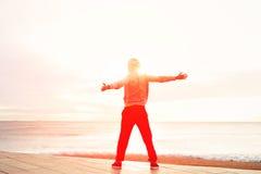 Allungamenti dell'uomo dopo avere corso al tramonto Fotografia Stock