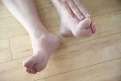 Allungamenti dell'uomo più anziano per toccare il suo dito del piede Fotografie Stock