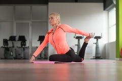 Allungamenti della donna di forma fisica al pavimento Fotografia Stock