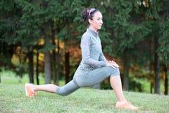 Allungamenti della donna di forma fisica durante l'allenamento di addestramento all'aperto Fotografie Stock