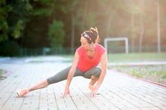 Allungamenti della ragazza di forma fisica per l'allenamento di formazione all'aperto Fotografie Stock Libere da Diritti