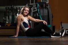 Allungamenti delle giovani donne nel club di forma fisica Fotografia Stock
