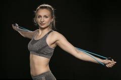 Allungamenti ed esercizi atletici della ragazza con una corda flessibile Immagini Stock