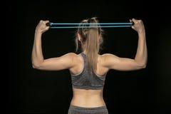 Allungamenti ed esercizi atletici della ragazza con una corda flessibile Fotografie Stock