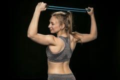 Allungamenti ed esercizi atletici della ragazza con una corda flessibile Immagini Stock Libere da Diritti