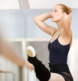 Allungamenti femminili lei stessa del ballerino di balletto vicino alla sbarra Fotografia Stock