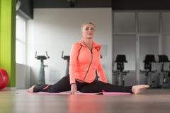 Allungamenti sani della donna al pavimento Fotografie Stock