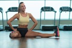 Allungamenti sani della giovane donna al pavimento Fotografia Stock