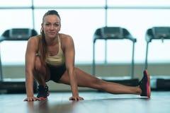 Allungamenti sani della giovane donna al pavimento Immagine Stock