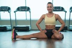Allungamenti sani della giovane donna al pavimento Fotografia Stock Libera da Diritti