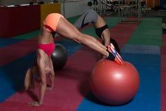 Allungamenti sportivi delle coppie della donna di misura sulla palla Fotografia Stock