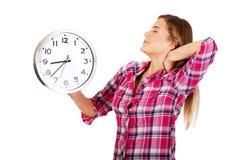 Allungamenti stanchi della donna e tenere un orologio Immagine Stock Libera da Diritti