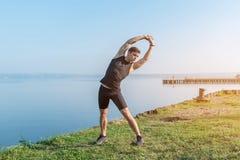 Allungamento adatto dell'uomo, esercitante addestramento sull'aria fresca Fotografia Stock Libera da Diritti