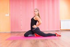 Allungamento adatto della donna suo indietro e gamba Fotografie Stock