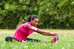Allungamento afroamericano del pareggiatore della donna - forma fisica, la gente e Fotografie Stock Libere da Diritti