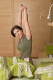 Allungamento alzantesi sorridente della donna Fotografia Stock