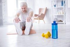 Allungamento anziano piacevole dell'uomo e dita del piede commoventi Fotografia Stock Libera da Diritti