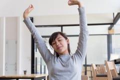 allungamento asiatico lei stessa della ragazza della studentessa fuori dopo avere svegliato Fotografie Stock