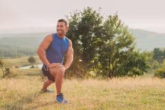Allungamento atletico dell'uomo all'aperto Immagine Stock