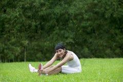 Allungamento attraente della donna esterno Fotografia Stock