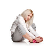Allungamento biondo di seduta della donna Immagine Stock