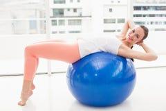 Allungamento castana adatto su una palla di esercizio Immagine Stock