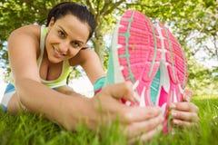 Allungamento castana atletico sorridente sull'erba Immagine Stock
