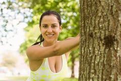Allungamento castana di misura felice contro un albero Immagine Stock