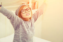 Allungamento d'uso del maglione della bella giovane donna sul letto in Fotografia Stock