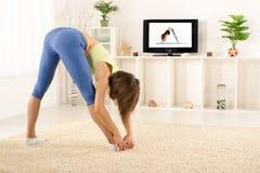 Allungamento degli esercizi in Front Of TV Fotografia Stock Libera da Diritti