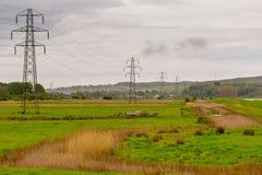 Allungamento dei piloni di elettricità attraverso un paesaggio rurale Fotografia Stock
