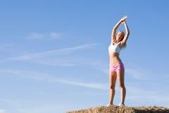 Allungamento del cielo blu adatto di estate della donna di sport Immagine Stock Libera da Diritti