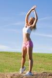 Allungamento del cielo blu adatto di estate della donna di sport Immagini Stock
