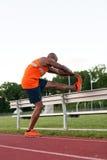 Allungamento del corridore di atletica Immagini Stock Libere da Diritti