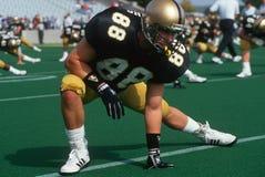 Allungamento del giocatore di football americano dell'istituto universitario Fotografia Stock