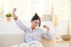 Allungamento del pigiama da portare della donna giovane Immagini Stock