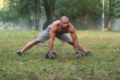 Allungamento dell'allenamento di esercizio all'aperto con le teste di legno Fotografia Stock