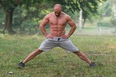 Allungamento dell'allenamento di esercizio all'aperto in parco Immagini Stock Libere da Diritti