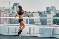 Allungamento della donna di forma fisica del tetto Fotografia Stock