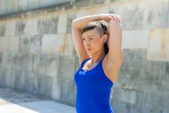 Allungamento della donna di forma fisica prima degli esercizi Immagine Stock