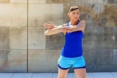 Allungamento della donna di forma fisica prima degli esercizi Fotografia Stock Libera da Diritti