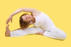 Allungamento della donna di yoga - donna isolata su fondo giallo Immagini Stock