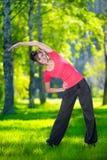 Allungamento della donna nell'esercizio di sport all'aperto. Fotografia Stock Libera da Diritti