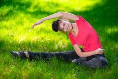 Allungamento della donna nell'esercizio di sport all'aperto. Fotografia Stock