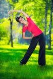 Allungamento della donna nell'esercizio di sport all'aperto Immagini Stock Libere da Diritti