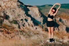 Allungamento della donna pronto risolvere all'aperto sulle montagne Fotografie Stock