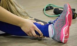Allungamento della gamba nella classe di forma fisica Immagini Stock