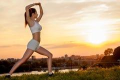 Allungamento della giovane donna all'aperto nel tramonto Fotografia Stock Libera da Diritti