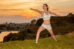 Allungamento della giovane donna all'aperto nel tramonto Immagine Stock